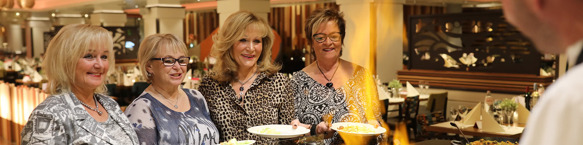 Vier Frauen stehen am Live-Cooking-Buffet in Egmond aan Zee