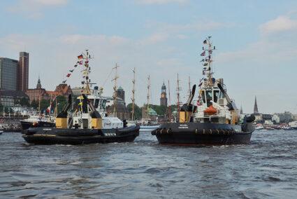 Zwei Schlepperboote fahren durch den Hamburger Hafen