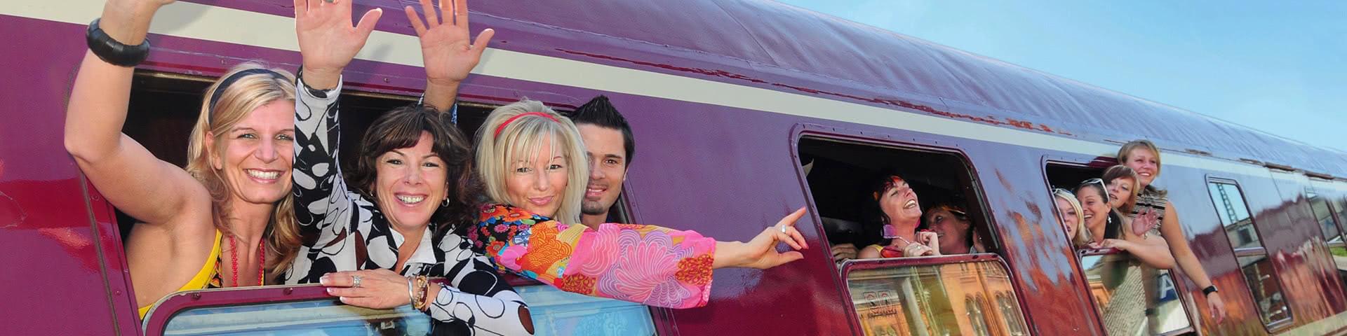 Feiernde Menschen winken aus dem Partyzug auf dem Weg nach Hamburg zur Schlagerparty
