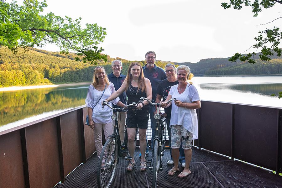 Gruppe macht Pause von einer Radtour an einer Aussichtsplattform am Hennesee