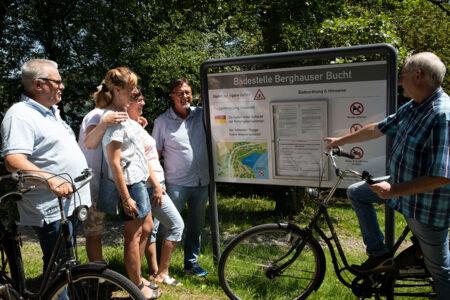 Gruppe schaut sich auf einer Fahrradtour am Hennesee gemeinsam eine Infotafel an