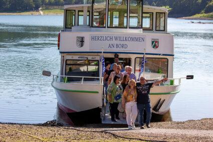 Gruppe verlässt gemeinsam ein Schiff am Ufer des Hennesee