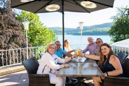 Gruppe sitzt auf Terasse mit Blick auf den Hennesee und stößt mit einem Bier an