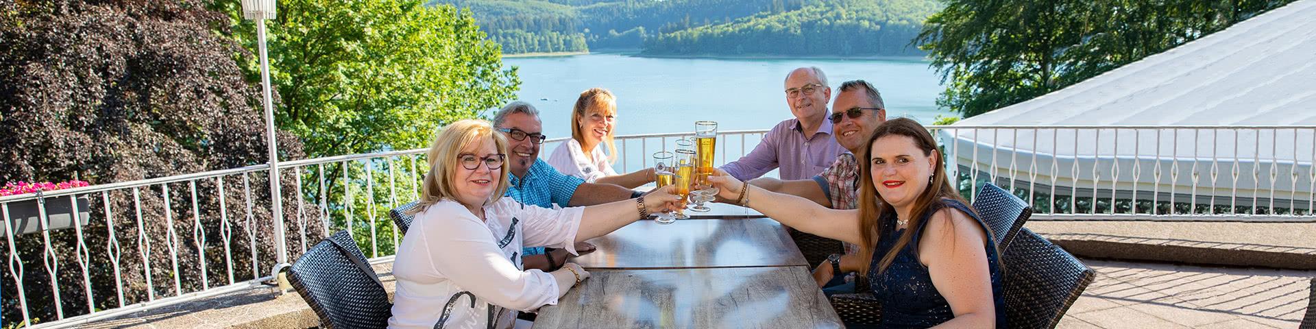 Gruppe trinkt gemeinsam Bier auf einer Terasse mit Blick auf den Hennesee