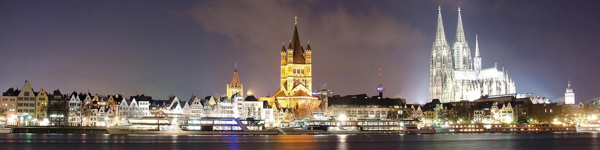 Schiffe auf dem Rhein vor der beleucteten Kölner Altstadt