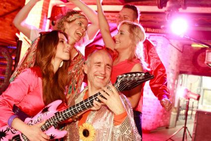 Fröhliche verkleidete Gruppe feiert Schlagerparty in Köln