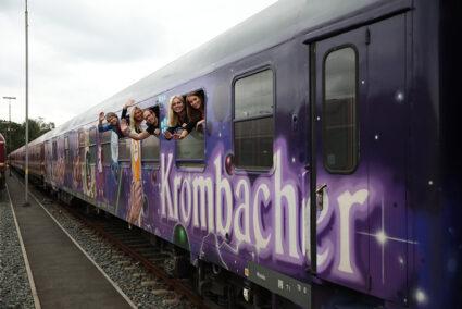 Fröhliche Gruppe winkt aus dem Krombacher Party-Express