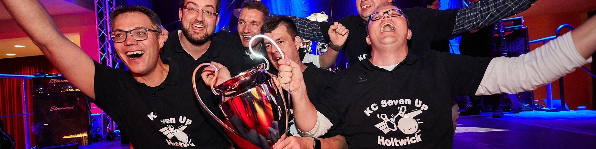Siegergruppe hält Pokal in den Händen bei der Kegelparty im Dorf Münsterland in Legden