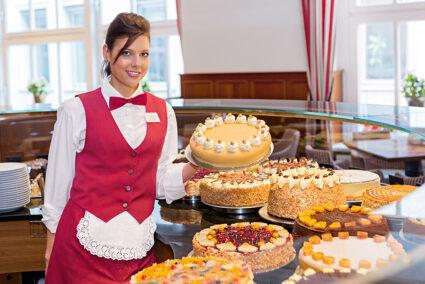 Frau steht an einem großen Kuchenbuffet in Lübeck