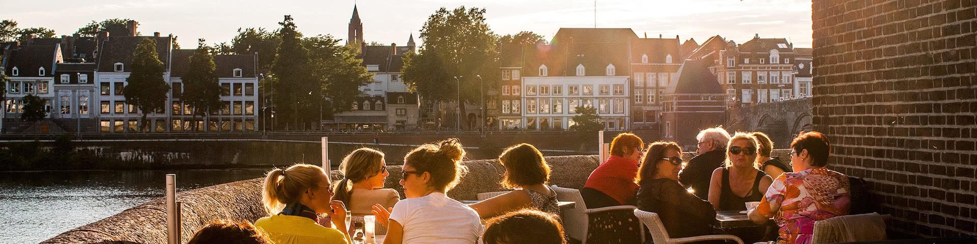 Menschen sitzen auf der Terasse vom Café Maas in Maastricht bei Sonnenuntergang