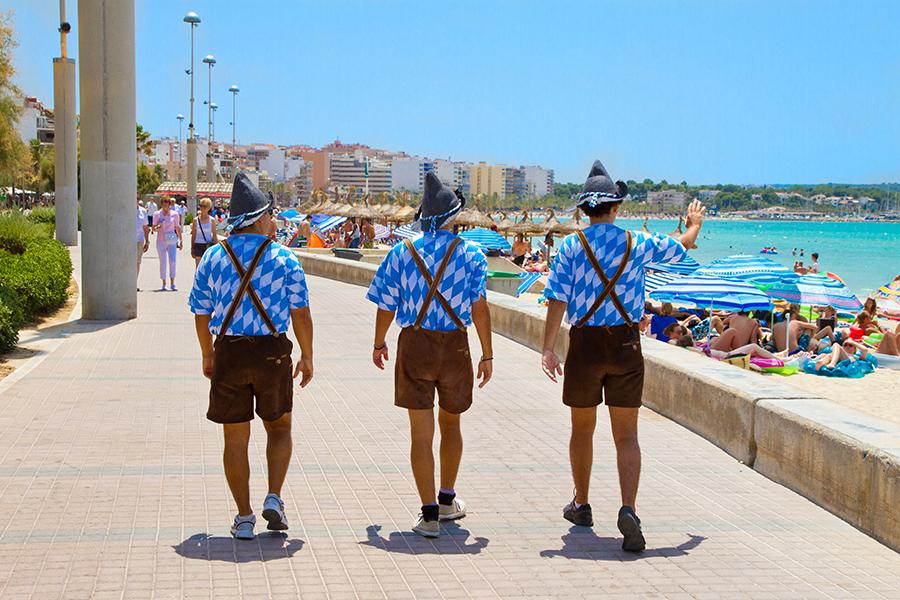 Drei Männer in Lederhosen läufen an der Strandpromenade auf Mallorca