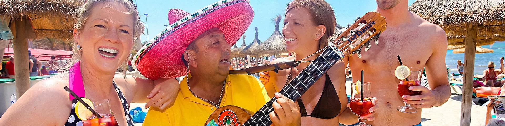 Gut gelaunte Gruppe mit einem Musikar am Strand auf Mallorca