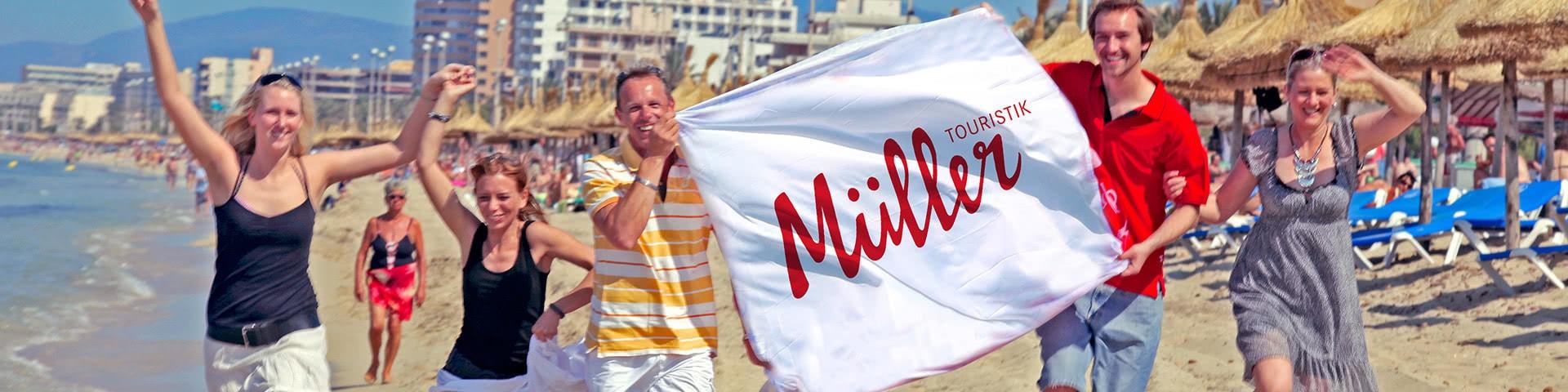 Gruppe läuft mit Müller-Touristik-Fahne am Strand von Mallorca
