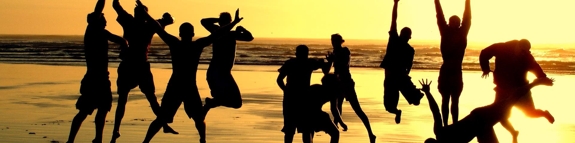 Gut gelaunte Gruppe am Strand bei Sonnenuntergang auf Mallorca