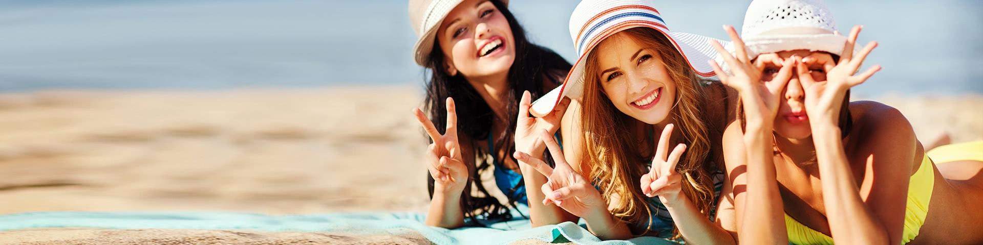 Drei fröhliche Frauen beim sonnen am Strand auf Mallorca
