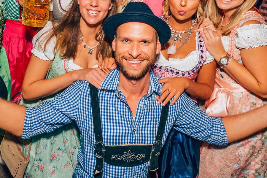 Mann in Tracht umgeben von Frauen im Dirndl auf dem Oktoberfest Münster