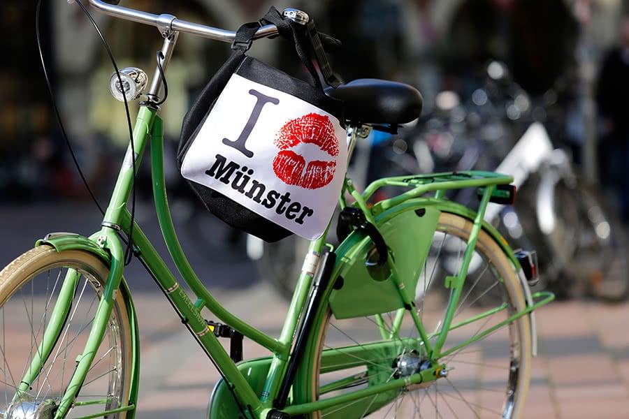 Grünes Fahrrad mit einer Münster-Tasche am Lenkrad