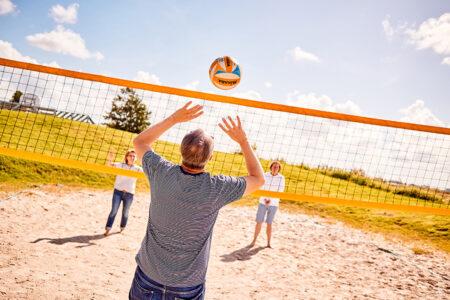 Gruppe spielt Beachvolleyball in Neuharlingersiel