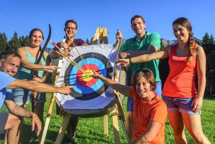 Gruppe steht zusammen einer Zielscheibe bom Bogenschießen in Neuharlingersiel
