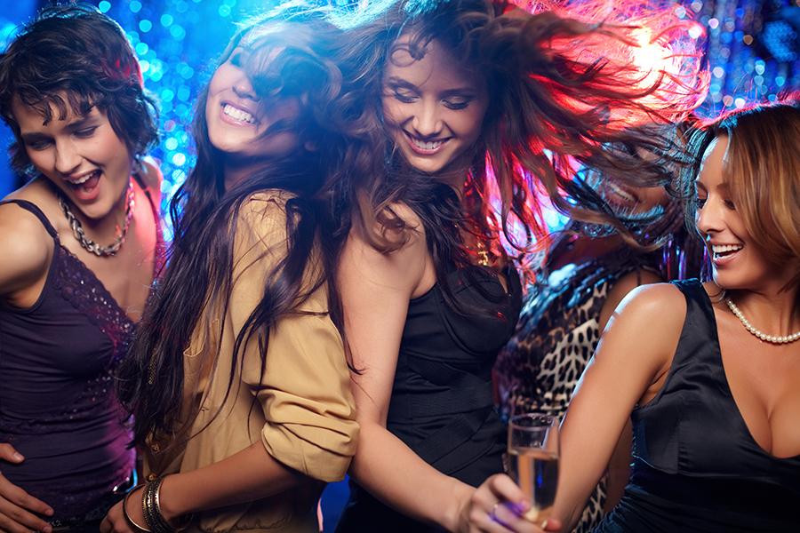 Vier junge Frauen tanzen ausgelassen in Neuharlingersiel