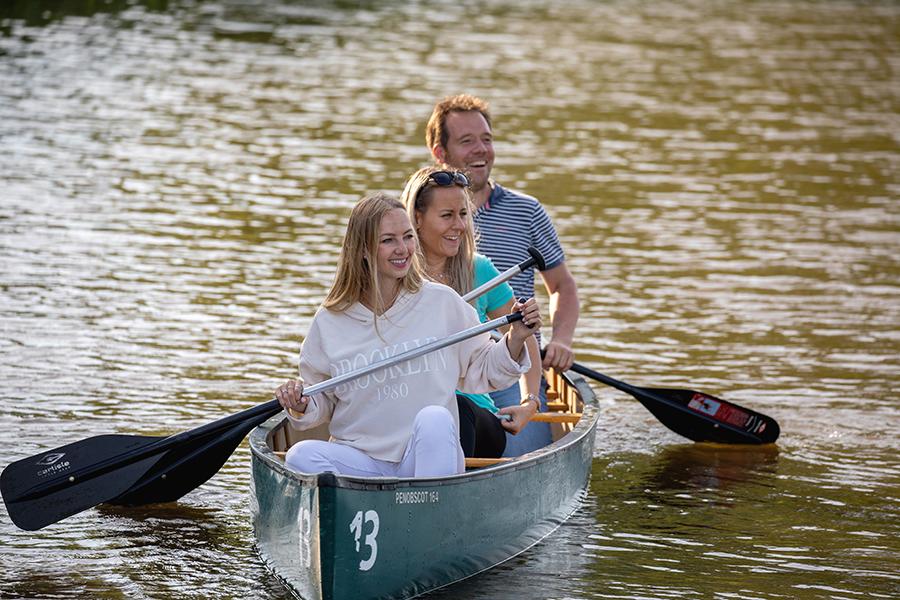Fröhliche Gruppe fährt Kanu in Neuharlingersiel