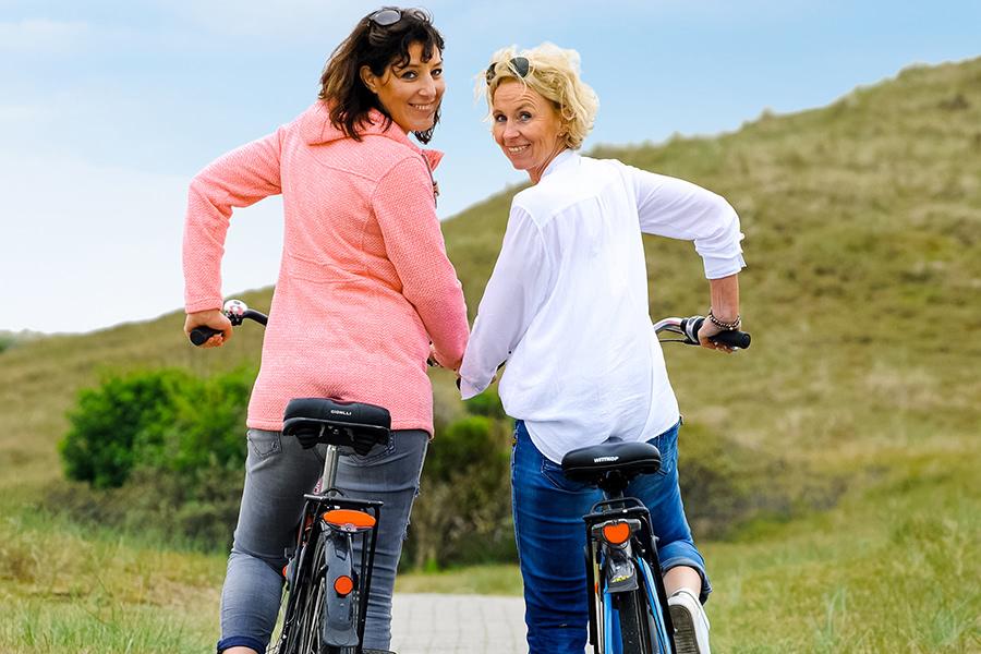 Zwei Frauen fahren gemeinsam Fahrrad auf Norderney