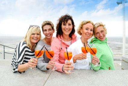 Frauengruppe trinkt gemeinsam Aperol am Strand von Norderney