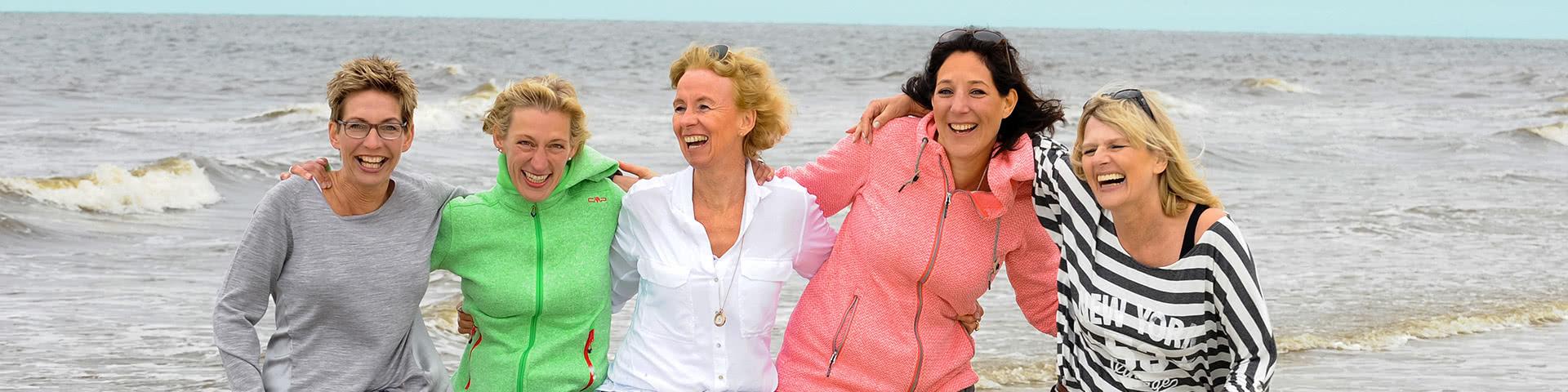 Gut gelaunte Frauengruppe steht am Meer auf Norderney