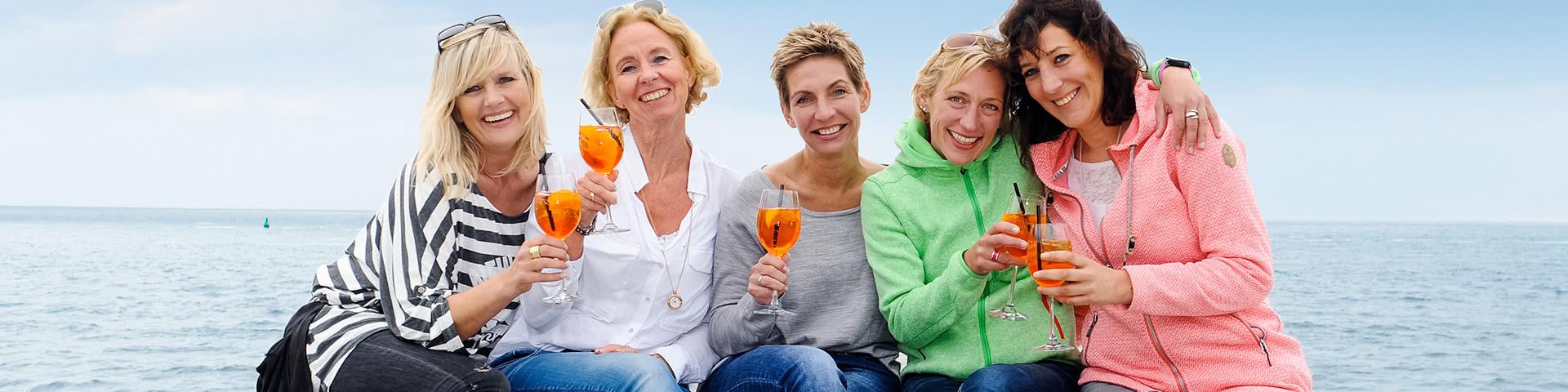 Frauengruppe trinkt gemeinsam Aperol Spritz am Strand von Norderney