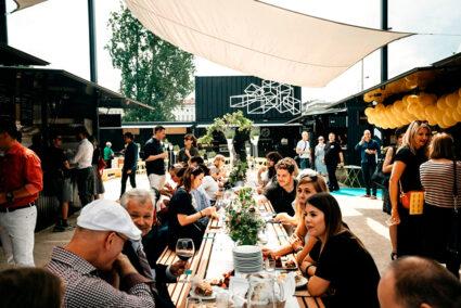 Menschen sitzen zusammen an einem langen TIsch auf dem Manifesto Market in Prag