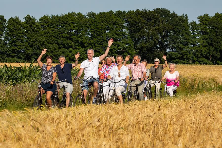 Eine Gruppe macht eine Radtour und fährt dabei auf einem Weg zwischen zwei Getreidefeldern