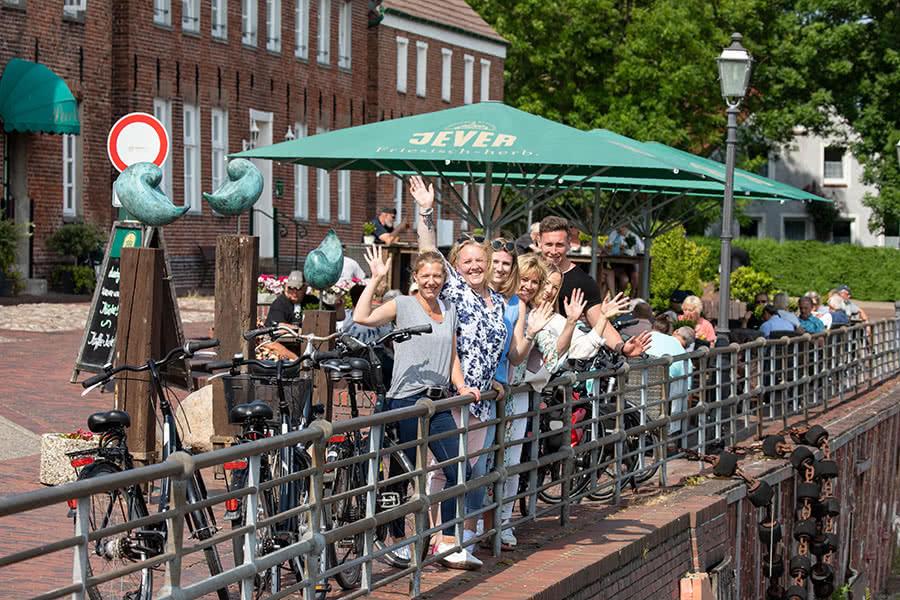 Eine Gruppe von 6 Personen steht an einem Geländer am Hafen und winkt
