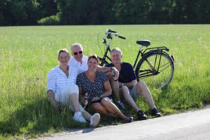 Zwei Paare sitzen mit Bier in der Hand am Straßenrand in einem Feld auf dem ein Fahrrad steht