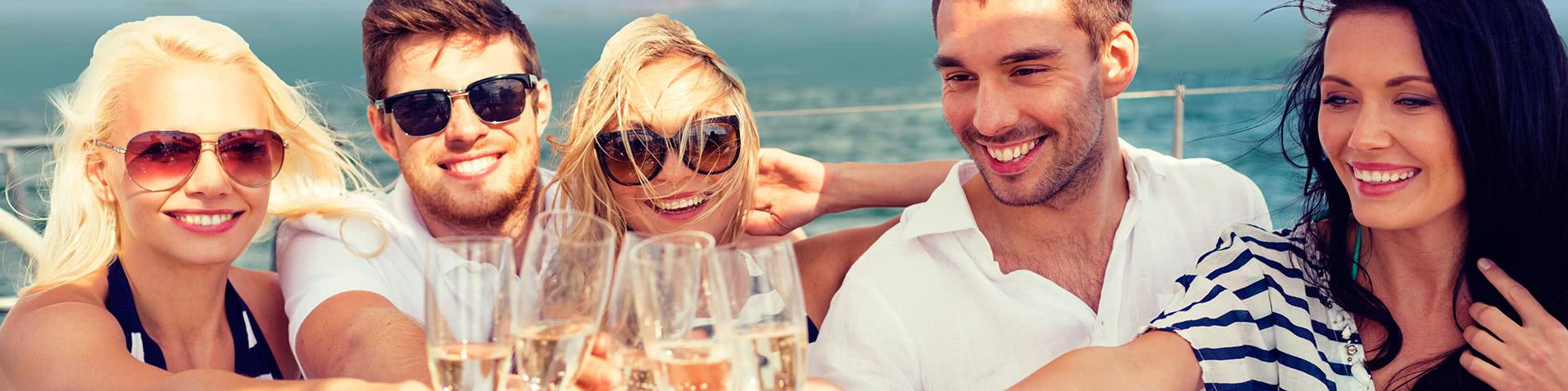 Gut gelaunte Gruppe trinkt gemeinsam Sekt auf dem Deck der MPS Statendam