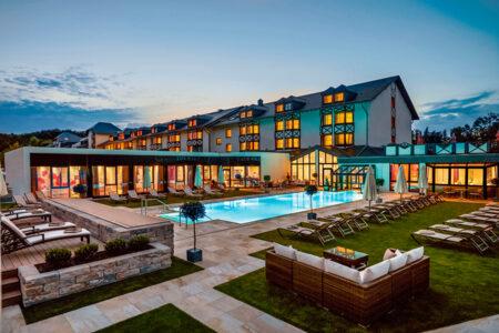 Außenansicht mit Pool Land & Golf Hotel Stromberg bei Dämmerung