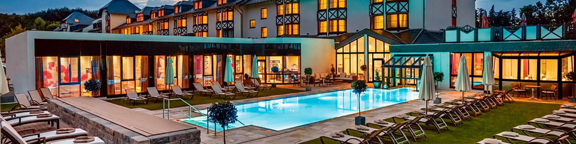 Außenansicht mit Pool vom Land & Golf Hotel Stromberg bei Dämmerung