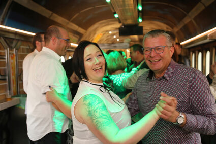 Personen tanzen im Tanzwagen im Zug zum Egmonder Schlagerfinale