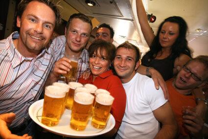 Eine Gruppe feiert im Tanzzug auf dem Weg nach Norderney eine Frau hält ein Tablett mit Bier