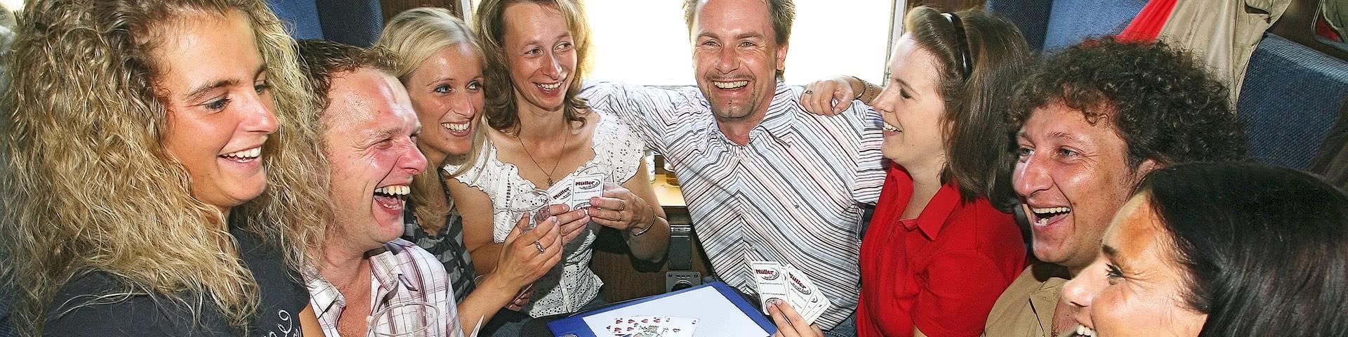 Eine Gruppe von 8 Personen sitzt in einem Sitzabteil des Tanzzuges und spielt Karten