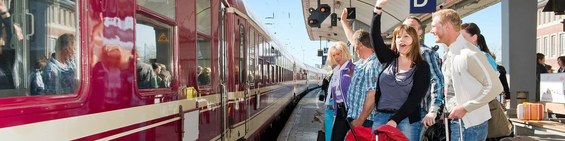 Eine Gruppe steht mit Gepäck am Bahnhofsgleis und winkt dem einfahrenden Tanzzug der ins Wangerland fährt