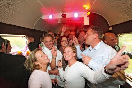 Leute feiern und tanzen im Tanzwagen des Tanzzuges