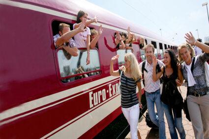 Menschen im Tanzzug winken den Menschen die am Bahnhof in den Tanzzug einsteigen werden