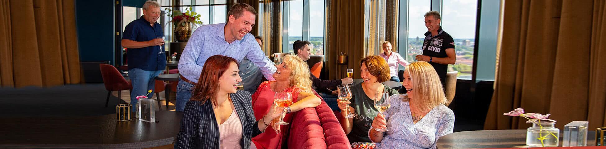 Lachende Gruppe sitzt in der Skybar im Van der Valk Hotel Tiel