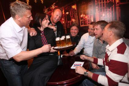 Kellnerin serviert Männergruppe Bier in Timmendorf