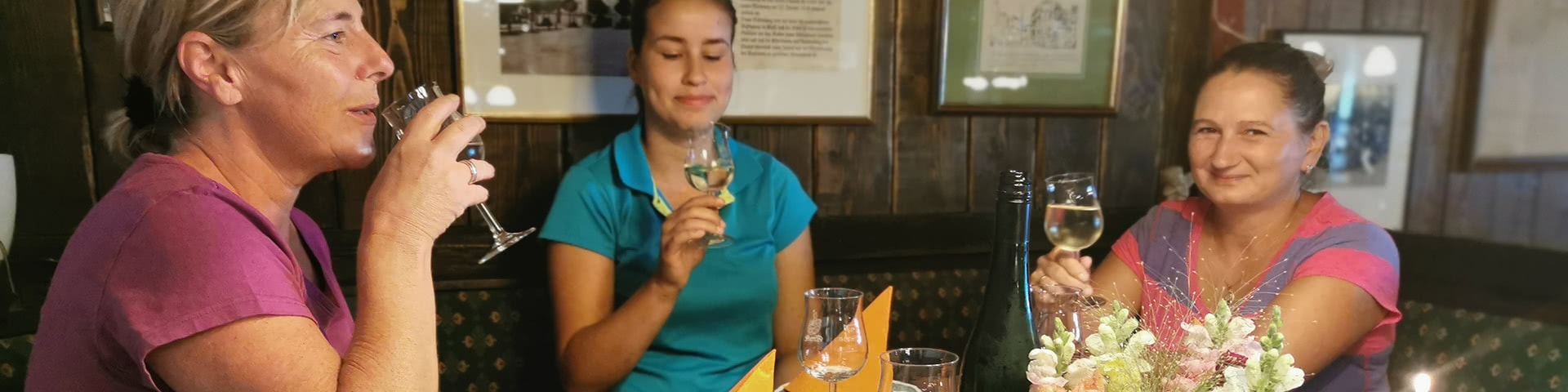 Drei Frauen trinken Wein auf einem Weingut in Trier