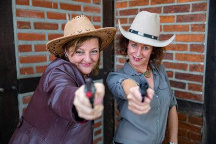 Zwei Frauen mit Cowboyhut und Spielzeugwaffe in der Hand im Wangerland