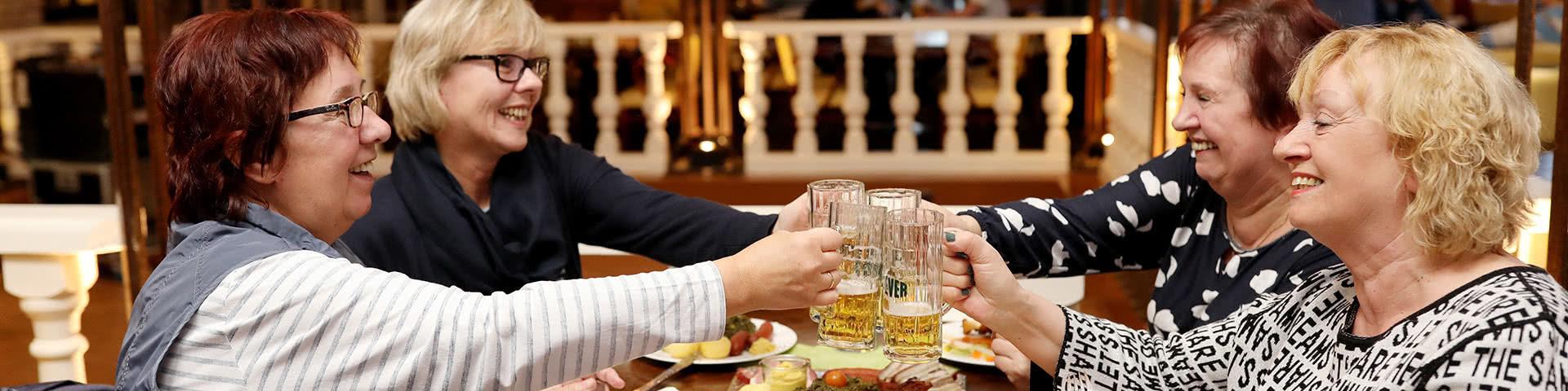 Gruppe stößt gemiensam mit Bier an beim Kohlessen im Wangerland