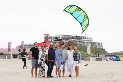 Gruppe steht am Strand von Wijk aan Zee und schaut auf das Meer