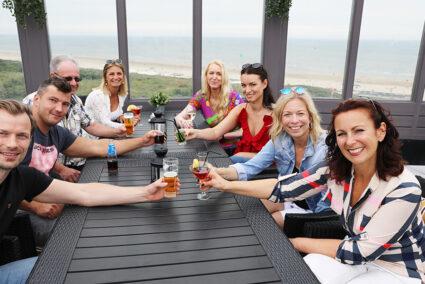 Gruppe sitz auf Terasse mit Merblick in Wijk aan Zee