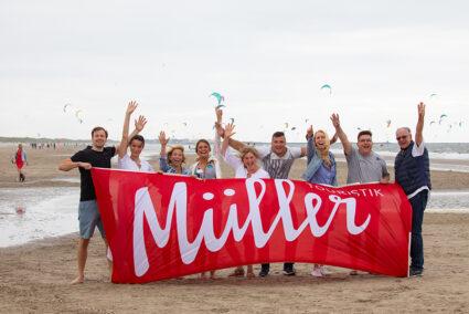 Gruppe steht am Strand in Wijk aan Zee und hält eine Müller-Touristik-Fahne